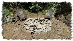 Large Stone Fire Pit Surrounded by Solar Lanterns that Illuminate at Night